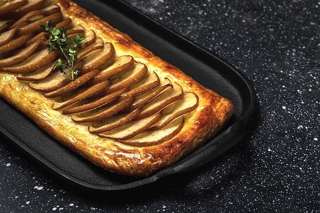Traditioneller hausgemachter bio-apfelkuchen auf dunklem tisch. gesundes foood-konzept