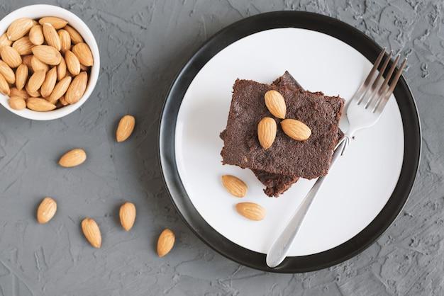 Traditioneller hausgemachter schokoladenbrownie, serviert auf einem teller mit gabel und mandelnüssen
