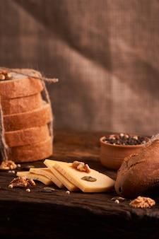 Traditioneller holländischer halb harter käse diente nah oben auf ländlicher tabelle mit dem rausschmiß. tiefenschärfe