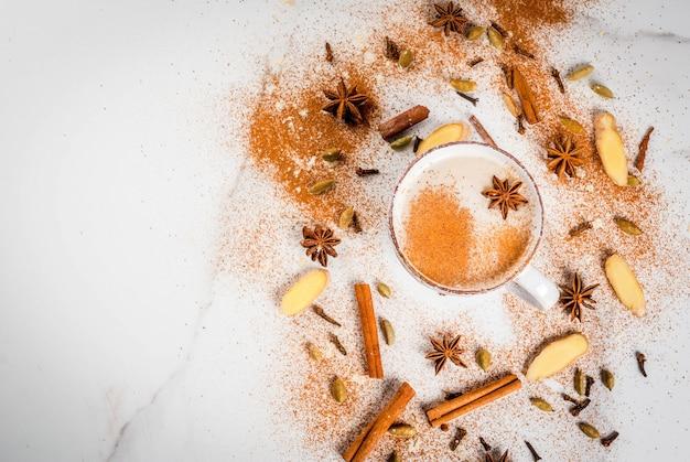 Traditioneller inder masala chai-tee mit gewürzen - zimt, kardamom, anis, weiß. draufsicht copyspace