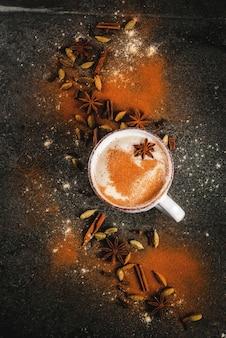 Traditioneller inder masala chai-tee mit gewürzzimt, kardamom, anis, dunkler stein. copyspace draufsicht
