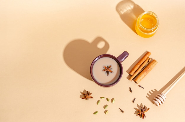 Traditioneller indischer tee. masala-tee in einer dunklen tonschale mit zutaten