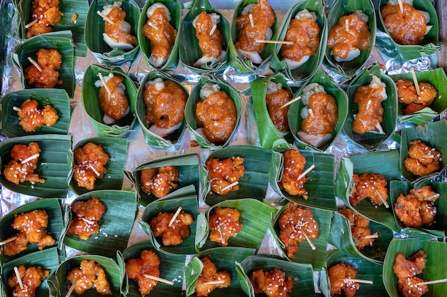 Traditioneller indonesischer snack in grünen palmblättern. nahaufnahme. asiatischer lebensmittelhintergrund, draufsicht, buffettisch