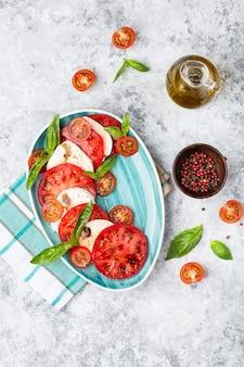 Traditioneller italienischer caprese-salat mit geschnittenen tomaten, mozzarella, basilikum, olivenöl
