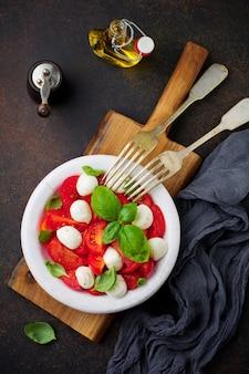 Traditioneller italienischer caprese-salat mit tomaten, mozzarella-käse und basilikum auf dunkler oberfläche in weißer alter keramikplatte. selektiver fokus. draufsicht.