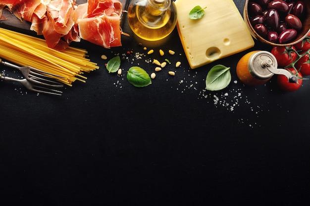 Traditioneller italienischer nahrungsmittelhintergrund mit spaghetti-tomaten-käseoliven und öl auf dunklem hintergrund.