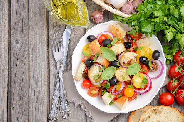 Traditioneller italienischer panzanellasalat mit frischen tomaten und knusprigem brot.