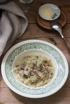 Traditioneller italienischer teller risotto mit champignons in einer hellen platte auf einem holztisch. rustikaler stil.