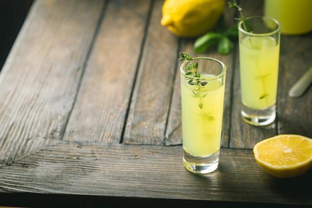 Traditioneller italienischer zitronenlikör limoncello und frische zitruszitrone. alkoholisches getränk.