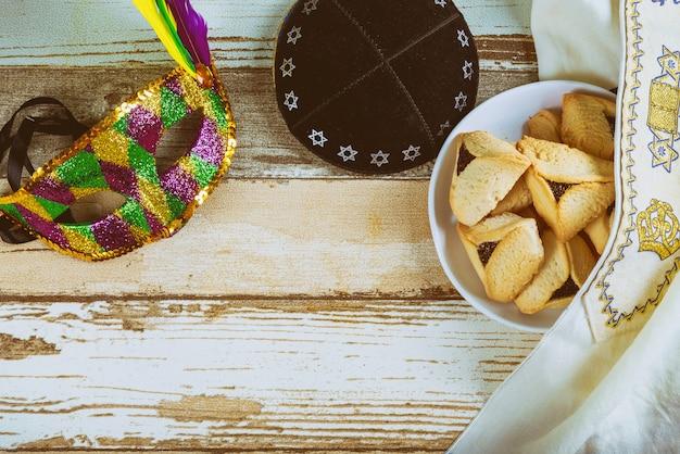 Traditioneller jüdischer karnevalsfeiertag purim-feier und hamantaschen plätzchen und maske, kippa