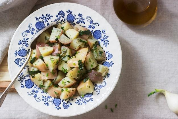 Traditioneller kalter kartoffelsalat mit zwiebeln und kräutern auf einem leinentischdeckenhintergrund. rustikaler stil.