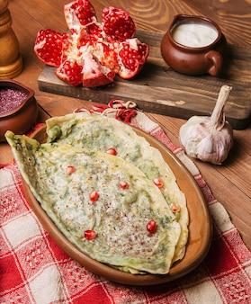 Traditioneller kaukasischer gemüsegutab, kutab, gozleme mit sumakh, granatsamen und joghurt in der hölzernen platte