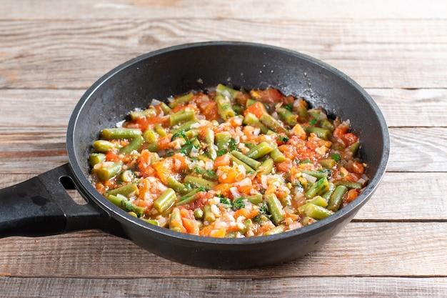 Traditioneller kaukasischer georgischer lobio aus grünen bohnen mit gemüse und tomaten in einer pfanne. schritt für schritt rezept. gesundes essen.