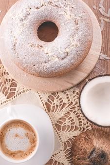 Traditioneller kokosnusskuchen und eine tasse milch mit kaffee großmutterkuchen