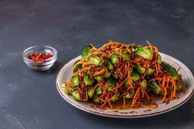 Traditioneller koreanischer gurkenkimchisnack: gurken angefüllt mit karotten, frühlingszwiebeln, knoblauch und indischem sesam, gegorenes gemüse, horizontales foto