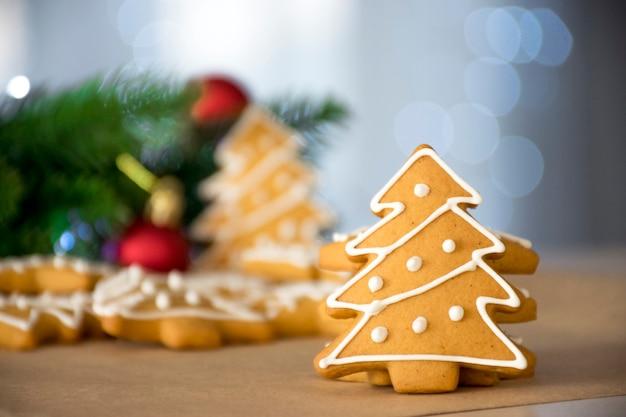Traditioneller lebkuchen in weihnachtsbaumform mit weißem zuckerguss- und tannenzweigrotspielzeug und bokehlichtern auf hintergrund