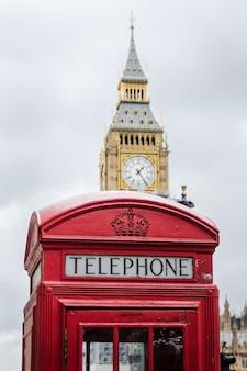Traditioneller londoner telefonkasten mit big ben im hintergrund