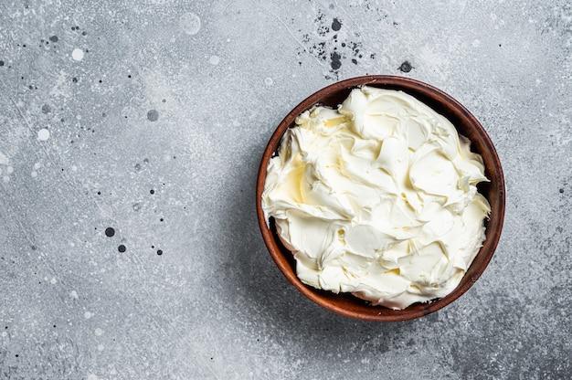 Traditioneller mascarpone-käse in holzschale. grauer hintergrund. ansicht von oben. platz kopieren.
