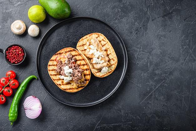 Traditioneller mexikanischer taco mit hühnchen und rindfleisch mit zutaten eine seite auf schwarzem teller über draufsicht des schwarzen strukturierten hintergrundes, mit platz für text.