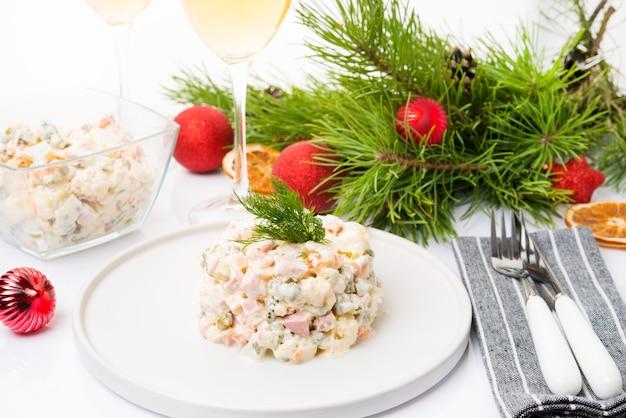Traditioneller neujahrssalat olivier mit festlicher dekoration auf weißem hintergrund, nahaufnahme