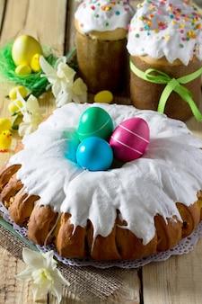 Traditioneller osterkuchen: der teig in einer rolle mit nussfüllung und rosinen, mit süßem zuckerguss. festlicher ostertisch.