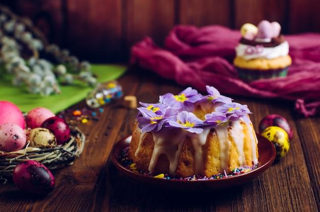 Traditioneller ostern-kuchen verziert mit primelblumen und gemalten eiern im natürlichen nest