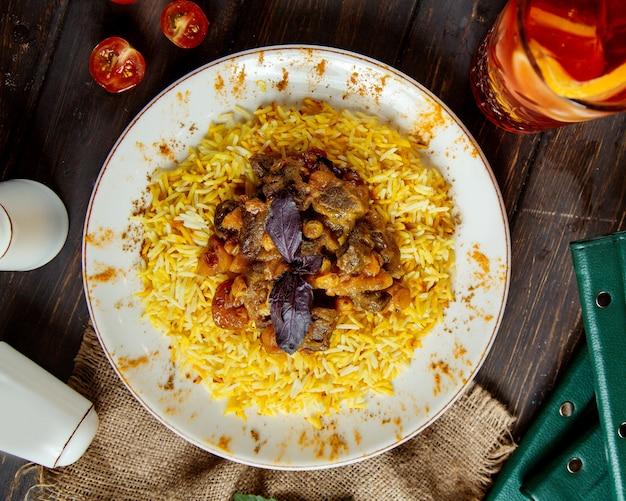 Traditioneller pilaw mit fleisch und gekochten früchten