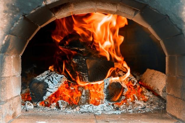 Traditioneller pizzaofen in ein hölzernes feuer im restaurant