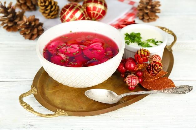 Traditioneller polnischer klarer roter borschtsch mit knödeln in schüssel auf tablett und weihnachtsschmuck auf holzoberfläche