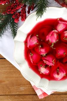 Traditioneller polnischer klarer roter borschtsch mit knödeln und weihnachtsdekorationen auf holztischoberfläche