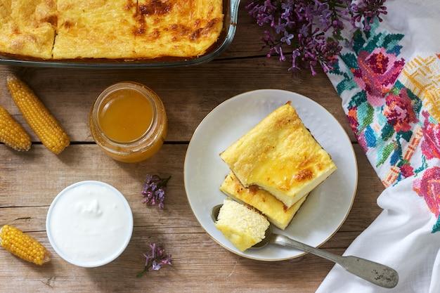 Traditioneller rumänischer oder moldauischer hüttenkäse-auflauf mit maismehl, serviert mit honig und sauerrahm.