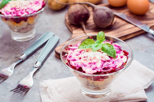 Traditioneller russischer aperitif des gekochten gemüses und der fische, des herings unter einem pelzmantel in den schüsseln und der bestandteile für auf dem tisch kochen. russischer salat
