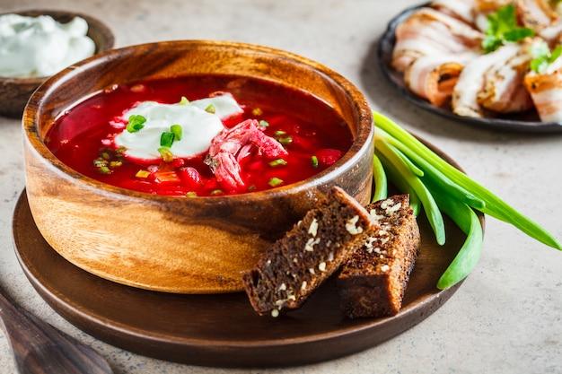 Traditioneller russischer borschtsch mit sauerrahm, roggenbrotkrumen und frühlingszwiebeln in der hölzernen schüssel. traditionelles russisches küchekonzept.