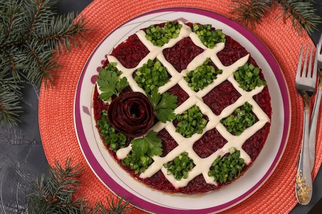 Traditioneller russischer feiertagssalat hering unter einem pelzmantel auf einem weihnachtshintergrund