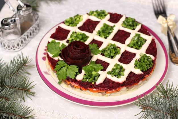 Traditioneller russischer feiertagssalat hering unter einem pelzmantel auf weihnachtshintergrund, nahaufnahme, horizontale ausrichtung
