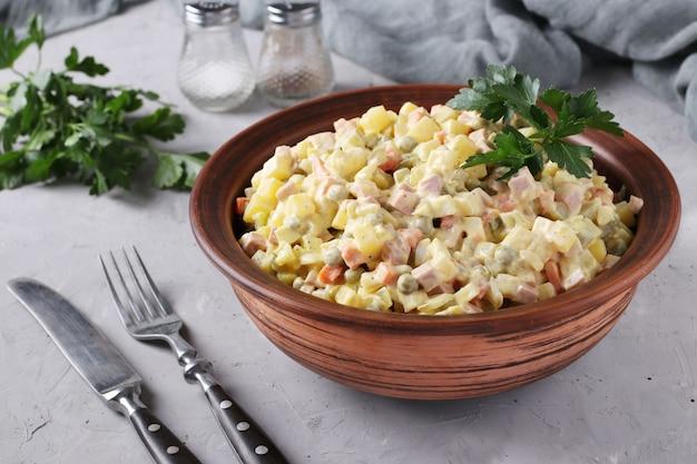 Traditioneller russischer festlicher salat olivier in der schüssel gegen graue oberfläche, nahaufnahme, horizontales format