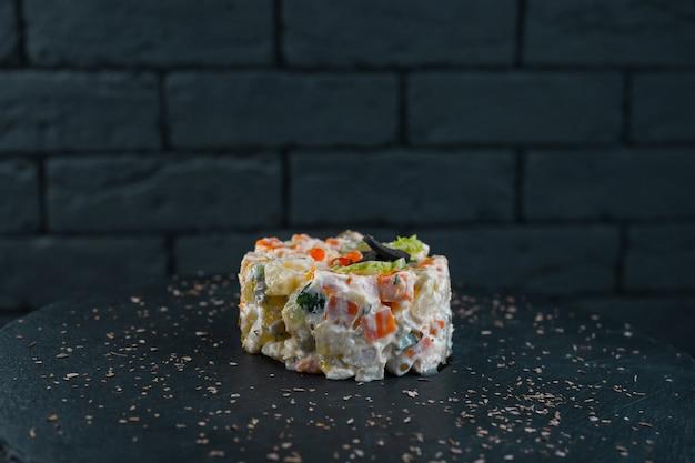 Traditioneller russischer köstlicher salat olivier mit wurst, mayonnaise, gemüse und gekochtem ei. die ursprüngliche portion essen im restaurant. festliches essen.