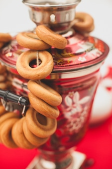 Traditioneller russischer messing malte samowar auf einer roten tischdecke, ein symbol der gastfreundschaft. knusprige bagels, trockenbagels oder bagels hängen am samowar