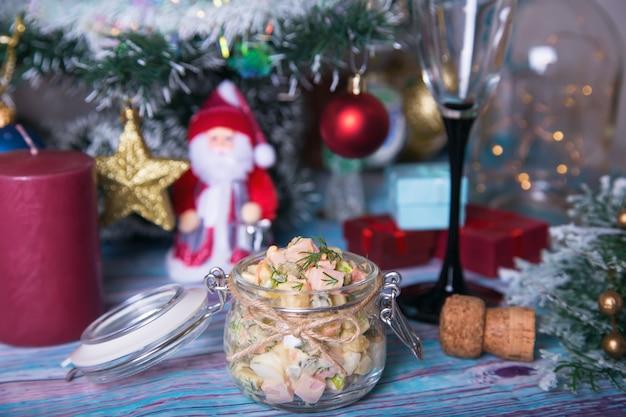 Traditioneller russischer neujahrs- und weihnachtssalat olivier (olivie) in einem glas. nahaufnahme, selektiver fokus.