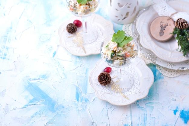Traditioneller russischer neujahrssalat aus gemüse und fleisch mit mayonnaise. in einem glas serviert und mit petersilie dekoriert, auf einem weißen tisch