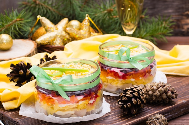 Traditioneller russischer salat, hering unter einem pelzmantel in schalen in neujahrsdekorationen