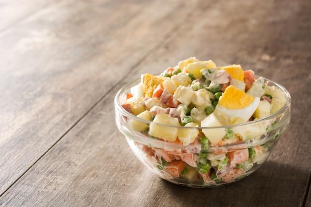 Traditioneller russischer salat in schüssel olivier-salat auf holztisch