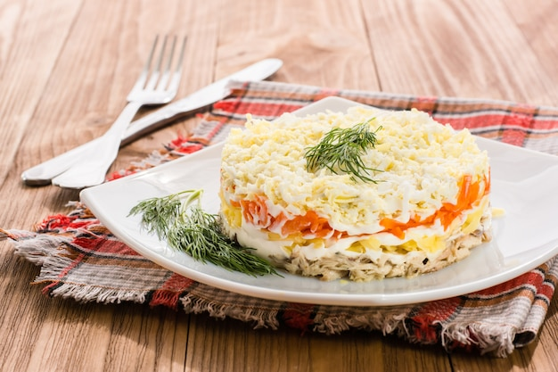 Traditioneller russischer salat mit gemüse und sardinen