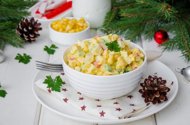 Traditioneller russischer salat mit krabbenstöcken, frischen gurken, mais und gekochten eiern in einer schüssel für neujahr und weihnachten.