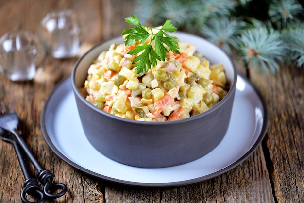 Traditioneller russischer salat olivier auf einer alten holzoberfläche. russische küche.