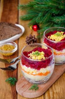 Traditioneller russischer salathering unter einem pelzmantel in einem glas für neues jahr und weihnachten