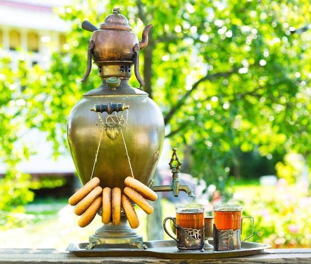 Traditioneller russischer tee mit samowar im garten