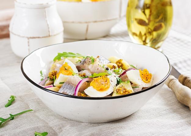 Traditioneller salat aus gesalzenem heringsfilet, frischen äpfeln, roten zwiebeln und eiern.