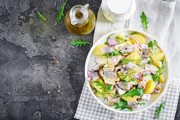Traditioneller salat aus gesalzenem heringsfilet, frischen äpfeln, roten zwiebeln und kartoffeln.