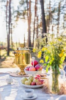 Traditioneller samowar auf dem tisch mit äpfeln und blumen im freien